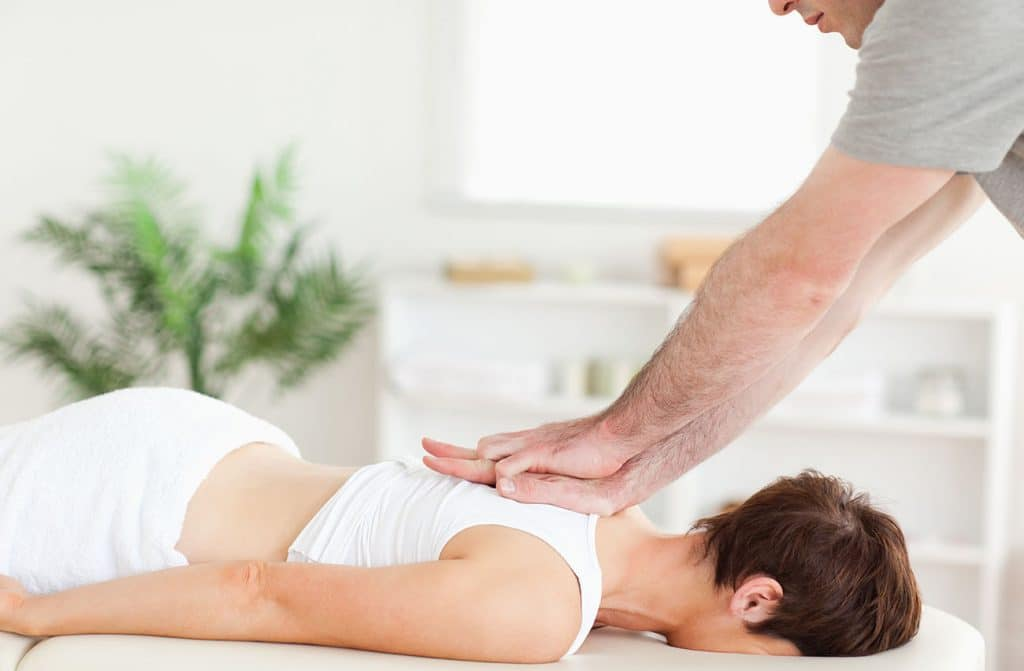 Woman receiving acupuncture and chiropractic care