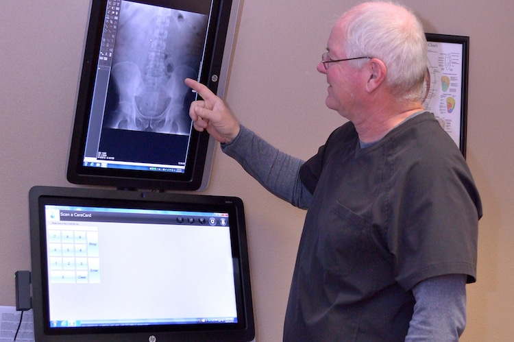Dr. Randy Hinze, a chiropractor in Columbus, discussing his findings with one of his patients.