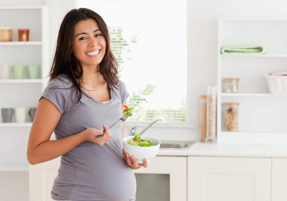 pregnant woman with a salad in her hand and happy knowing that she can receive chiropractic care throughout her pregnancy in columbus with Dr. Hinze