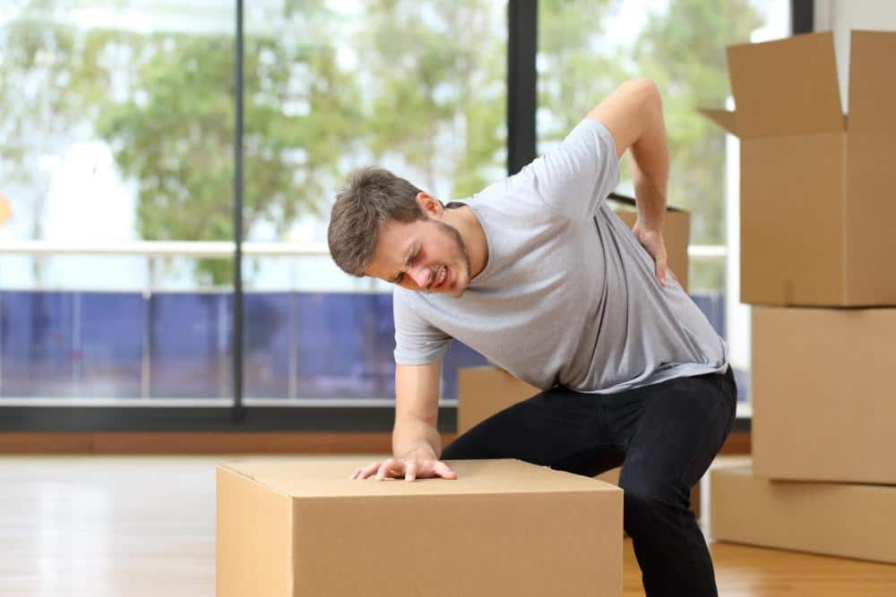 Man experiencing back pain from lifting boxes improperly.