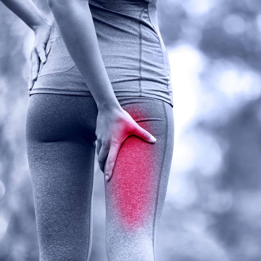 Female holding her right leg due to sciatic leg pain.