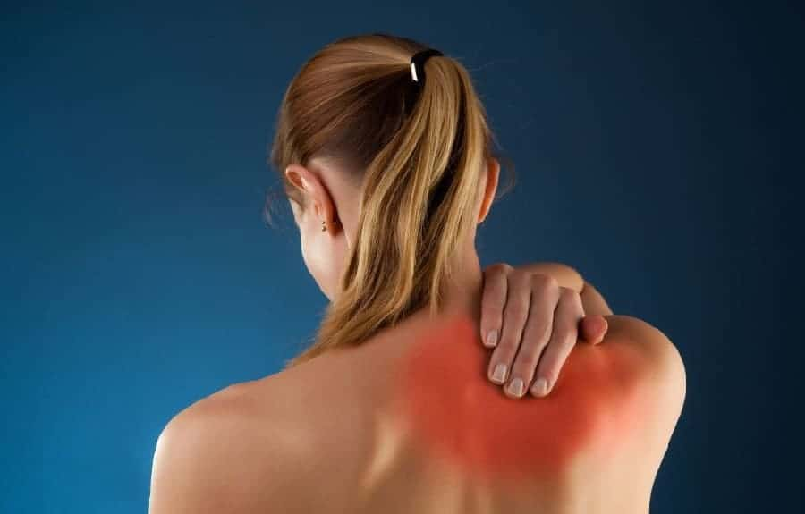 Back view of a woman holding with a pinched nerve at her right shoulder blade. Treatment available at Hinze Chiropractic and Acupuncture in Columbus