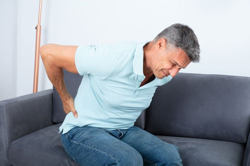 Senior man in pain sitting while holding his back due to pinched nerve.