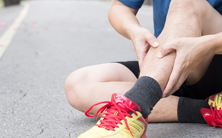 Runner sitting on the ground while holding his painful leg.